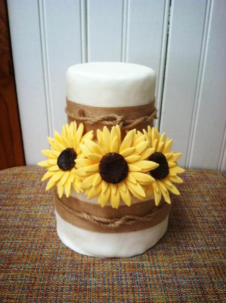 A small two-tier rustic wedding cake with sunflowers